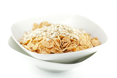 Muesli. And corn flakes in white plates on white background Royalty Free Stock Image