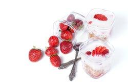 Muesli, aardbeien en yoghurt op een witte achtergrond Stock Foto