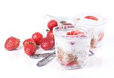 Muesli, aardbeien en yoghurt op een witte achtergrond in glazen Royalty-vrije Stock Afbeeldingen