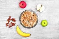 Muesli avec la banane, la pomme et les écrous Bol de gruau avec les fruits et le lait sur le fond gris en bois Petit déjeuner sai Photographie stock