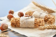 Muesli bars with wheatear. Two muesli bars with filbert nuts and wheatear on backing parchment background Royalty Free Stock Photos