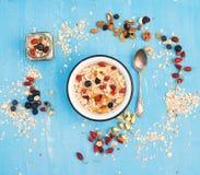 Muesli, bayas con las nueces y las semillas en cuenco en backg rústico azul Fotografía de archivo libre de regalías
