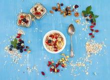 Muesli, bayas con las nueces y las semillas en cuenco en backg rústico azul Foto de archivo libre de regalías