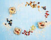 Muesli, bayas con las nueces y las semillas en fondo rústico azul - Fotos de archivo libres de regalías