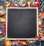 Muesli and berries around black blank chalkboard background. Healthy breakfast concept. Detox and Clean food concept Royalty Free Stock Photography