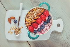 Muesli berries and smoothie. Healthy classic breakfast with oatmeal and various fresh berries, almonds, chia grains and corn flakes in a bowl, top view Royalty Free Stock Photo