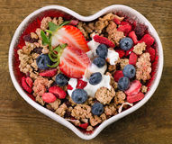Muesli with berries and yogurt in heart shaped bowl. Royalty Free Stock Images