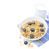 Muesli with blueberries and jug of milk, isolated Royalty Free Stock Image