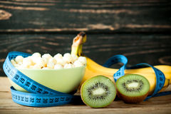 Muesli in bowl and fresh fruits with measuring tape Stock Image