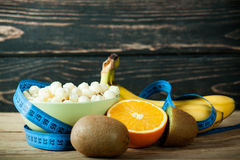 Muesli in bowl and fresh fruits with measuring tape Royalty Free Stock Images
