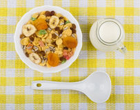 Muesli in bowl and jug milk on yellow tablecloth Royalty Free Stock Photos