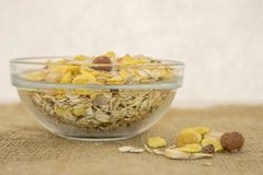 Muesli in a bowl on a rustic background. Healthy breakfast muesli with dried fruit on a rustic background of jute Royalty Free Stock Photos