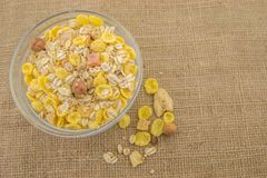 Muesli in a bowl on a rustic background. Healthy breakfast muesli with dried fruit on a rustic background of jute Stock Photography