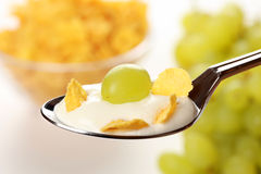 Muesli for breakfast. Close-up of a spoon with fresh yoghurt, corn flakes and a grape stock image