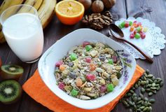 Muesli with candied fruits and nuts with a glass of milk on a dark wooden table royalty free stock images