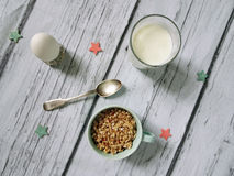 Muesli, cereal in cup, milk and egg. healthy breakfast scene on white wooden background. Top view photo.  Royalty Free Stock Images