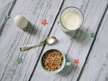 Muesli, cereal en taza, leche y huevo escena sana del desayuno en el fondo de madera blanco Foto de la visión superior Imágenes de archivo libres de regalías