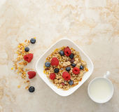 Muesli cereal with raspberries and blueberries. Mug of milk. Hea Royalty Free Stock Photo
