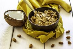 Muesli with coconut and banana on a white wooden backdrop. stock image