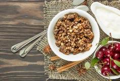Muesli con crema y cerezas para el desayuno en un backgro de madera Foto de archivo libre de regalías