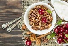 Muesli con la salsa y las cerezas rojas para el desayuno en un CCB de madera Fotos de archivo