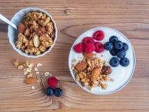 Muesli con las frutas frescas en una tabla de madera, visión superior foto de archivo