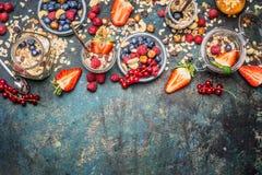 Muesli con le bacche, i dadi ed i semi freschi Ingredienti equilibrati della prima colazione su fondo rustico Fotografie Stock