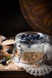 Muesli con yogurt e le bacche blu in barattolo di vetro Immagini Stock