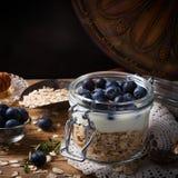 Muesli con yogurt e le bacche blu in barattolo di vetro Fotografia Stock
