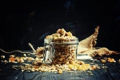 Muesli cozido com passas e sementes de girassol em um frasco de vidro, bl foto de stock