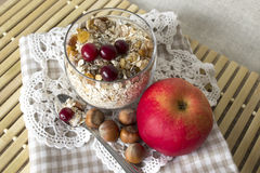 Muesli with cranberries, apples and nuts in a glass. Muesli in a glass with cranberries, apples and nuts on a lace base Stock Images