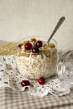 Muesli with cranberries in a glass. Muesli in a glass with cranberries, apples and nuts on a lacy napkin Royalty Free Stock Photography