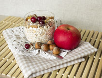 Muesli with cranberry apple and nuts in a glass. On lacy napkin and a wooden stand Royalty Free Stock Photos