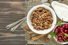 Muesli with cream and cherries for breakfast on a wooden backgro. Homemade granola with cream, cinnamon and cherries for breakfast on a wooden background Royalty Free Stock Photo