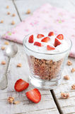 Muesli with cream and strawberry on wooden table Royalty Free Stock Photos