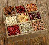 Muesli, dadi e bacche in una scatola di legno Immagini Stock