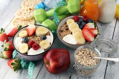 Muesli with dairy and fruit, healthy lifestyle. bowl of cereal, fruit and dumbbell. Muesli with dairy and fruit, healthy lifestyle. bowl of cereal, fruit and Royalty Free Stock Photos