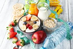 Muesli with dairy and fruit, healthy lifestyle. bowl of cereal, fruit and dumbbell.. Muesli with dairy and fruit, healthy lifestyle. bowl of cereal, fruit and Stock Photography