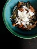 Muesli dans la cuvette verte avec la noix de coco, amandes, graines de citrouille Photo libre de droits