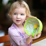 Muesli de consommation de petite fille avec du yaourt pour le petit déjeuner Photographie stock libre de droits