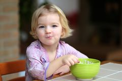 Muesli de la consumición de la niña con el yogur para el desayuno Fotografía de archivo