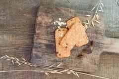 Muesli de las galletas hecho con la harina de arroz orgánica cruda de los cereales con el chocolate en vieja tabla de cortar de m Imagen de archivo libre de regalías