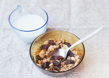 Muesli with dried fruit in a bowl and glass of milk Stock Image