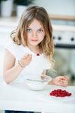 Muesli Essen des jungen Mädchens mit Himbeeren stockfoto