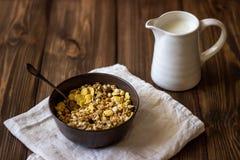Muesli et cruche de lait sur un fond en bois Type rustique photo stock