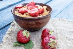 Muesli fait maison frais, muesli avec des fraises dans un plat sur un fond bleu images libres de droits