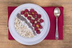 Muesli fez da framboesa, dos flocos da aveia, das sementes do chia com iogurte e do mel, fim acima, vista superior Foto de Stock Royalty Free