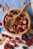 Muesli with fresh berries close up in a wooden bowl. Vertical to. Muesli with fresh berries close up in a wooden bowl on the table. Vertical top view Royalty Free Stock Photography