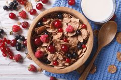 Muesli with fresh berries and milk on the table. Horizontal top. Muesli with fresh berries in a wooden bowl and milk on the table. horizontal top view Royalty Free Stock Photo