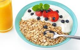 Muesli with fresh berries and yogurt in a bowl. Isolated on white background. Orange juice Stock Image